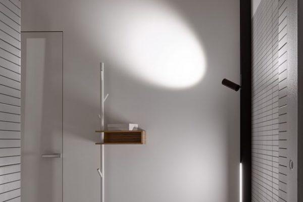房間的室內裝潢是柔和的灰色牆壁,深色調的室內設計家具和淺色木炭的透明窗簾。